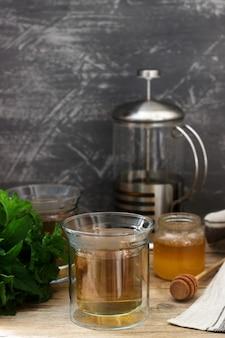 Tisane à base de menthe et mélisse avec du miel dans des tasses en verre. style rustique.