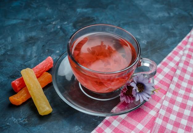 Tisane avec des bonbons, des fleurs dans une tasse sur bleu et torchon, vue grand angle.