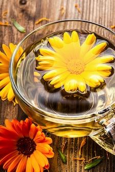 Tisane de calendula (marigold) dans une tasse en verre transparent avec des fleurs séchées sur fond rural en bois.