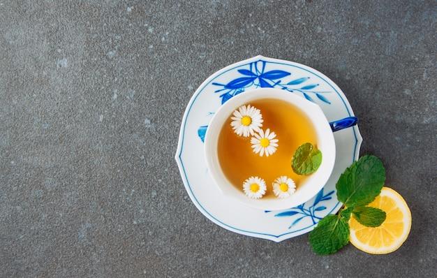 Tisane de camomille dans une tasse et une soucoupe avec la moitié du citron et des feuilles vertes à plat sur un fond de stuc gris