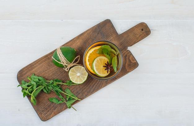 Tisane, citron vert et menthe sur une planche à découper