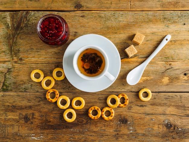 Tisane, confiture de framboises et bagels sur une vieille table en bois.