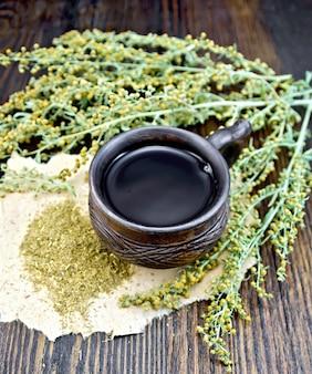 Tisane dans une tasse d'argile, brindilles d'armoise grise, absinthe séchée sur papier contre la planche de bois sombre