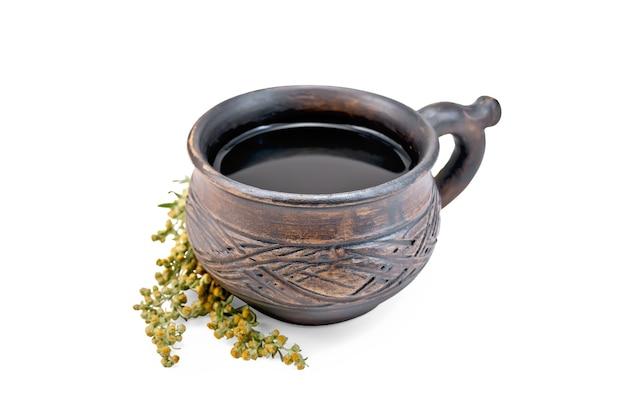 Tisane dans une tasse d'argile brune, brindilles d'absinthe grise isolée sur fond blanc