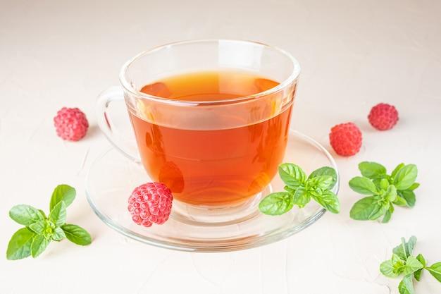 Tisane dans une tasse transparente avec une soucoupe sur un fond clair. autour - framboises fraîches et feuilles de menthe. concept de boissons vitaminées.