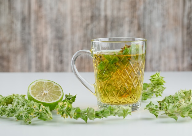 Tisane dans une tasse en verre avec des feuilles, vue côté citron vert sur blanc et grungy