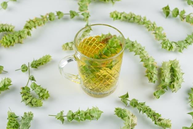 Tisane dans une tasse en verre avec des feuilles vue grand angle sur un blanc