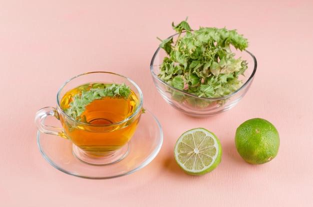 Tisane dans une tasse en verre avec des herbes, limes high angle view on a pink