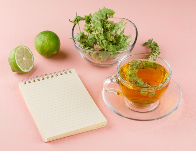 Tisane dans une tasse en verre avec des herbes, limes, notebook high angle view on a pink