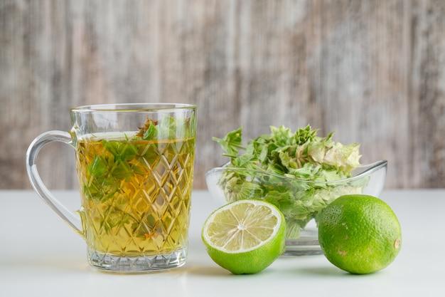 Tisane dans une tasse en verre avec des herbes, vue de côté de limes sur blanc et grungy