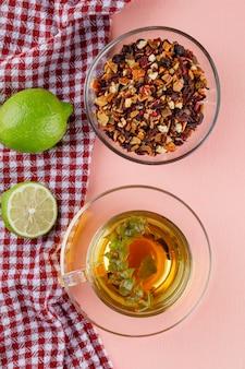 Tisane dans une tasse en verre avec limes, herbes séchées à plat sur rose et torchon
