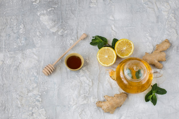 Sur une tisane à fond gris dans une théière transparente, gingembre, citron, miel et menthe