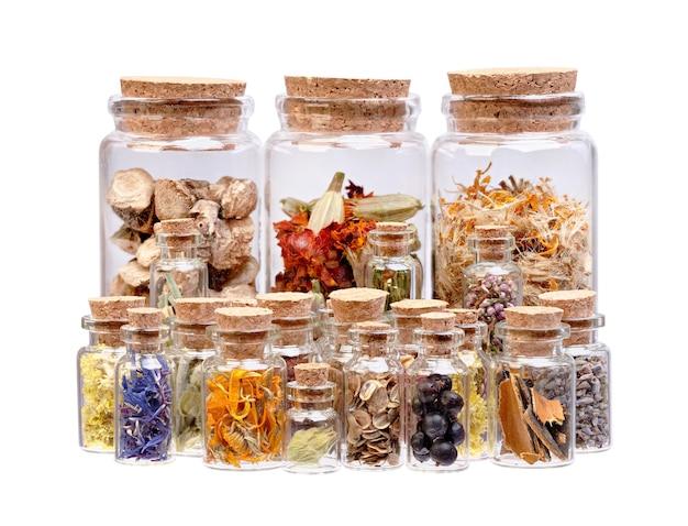 Tisane, herbes séchées, fleurs et baies dans des bouteilles en verre à usage médical isolées sur blanc.
