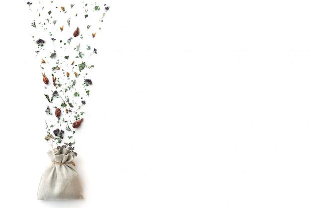 Tisane, plantes et fleurs sèches, origan et boisson vitaminée à la menthe dans un fond de sac en lin