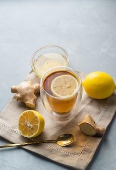 Tisane de vie saine thé au miel de citron avec racine de gingembre sur une surface grise