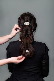 Tissage, coiffure de queue tressée. salon de coiffure faisant la coiffure aux cheveux bruns femme aux cheveux longs sur fond gris. services de coiffure professionnels processus de coiffure, fabrication de tresses avec épingle à cheveux