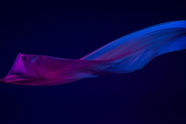 Tissu bleu transparent élégant lisse séparé sur bleu.