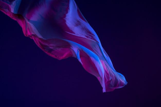 Tissu bleu transparent élégant lisse séparé sur fond bleu.