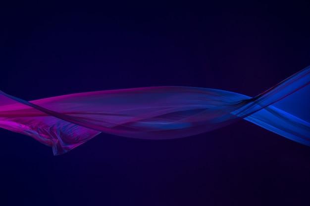 Tissu bleu transparent élégant et lisse séparé sur fond bleu.
