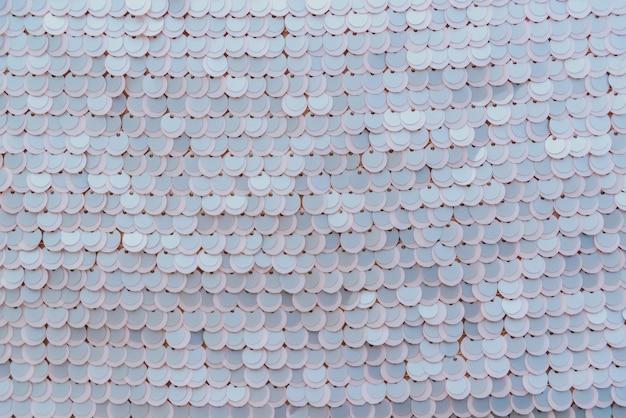 Tissu brillant rose pâle avec des paillettes, abstrait.