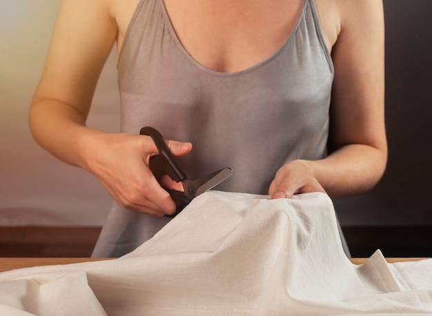 Tissu de coton de coupe de couturière avec le plan rapproché de mains de créateur de mode de ciseaux de couture