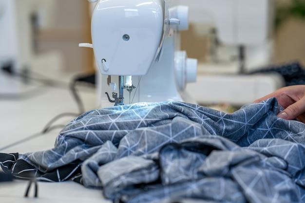 Tissu à coudre sur une machine à coudre dans un atelier de couture