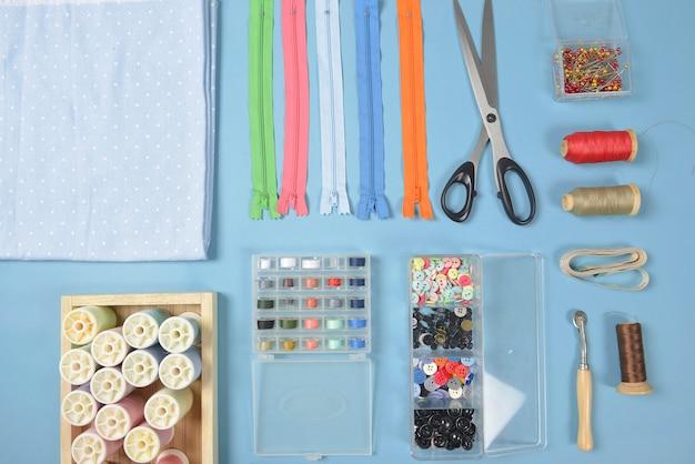 Le tissu à coudre à plat contient les tissus, les ciseaux, la fermeture à glissière, les aiguilles et les rouleaux de fil.