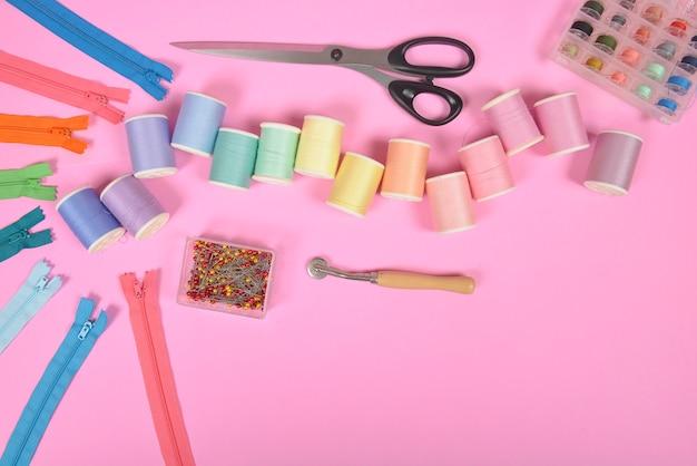Le tissu à coudre à plat contient les tissus, les ciseaux, la fermeture à glissière et les rouleaux de fil.