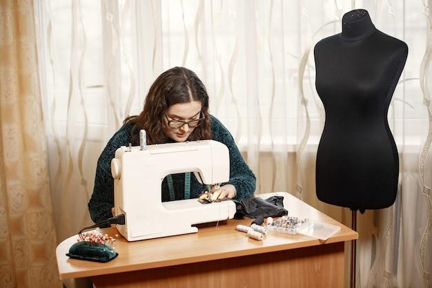 Tissu dans une machine à écrire. la femme travaille habilement avec une machine à coudre. femme à lunettes.