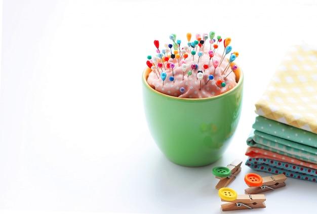 Tissu, épingles à linge décoratives et épingles multicolores à coudre sur un support spécial.