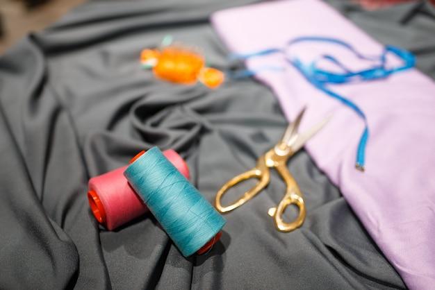 Tissu, fil et ciseaux dans un magasin de textile, personne. vitrine avec accessoires pour la couture, choix de vêtements en magasin