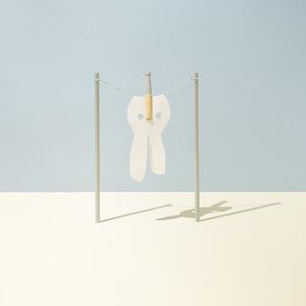 Le tissu en forme de lapin de pâques est fixé avec une pince à linge sur une corde à linge sur fond bleu pastel et jaune. concept minimaliste. disposition carrée