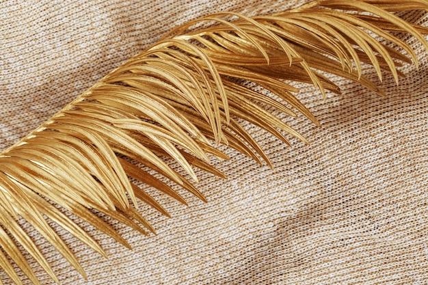 Tissu en laine avec gros plan de paume de feuille peinte. tissu tricoté et feuille d'or. contexte créatif d'automne.