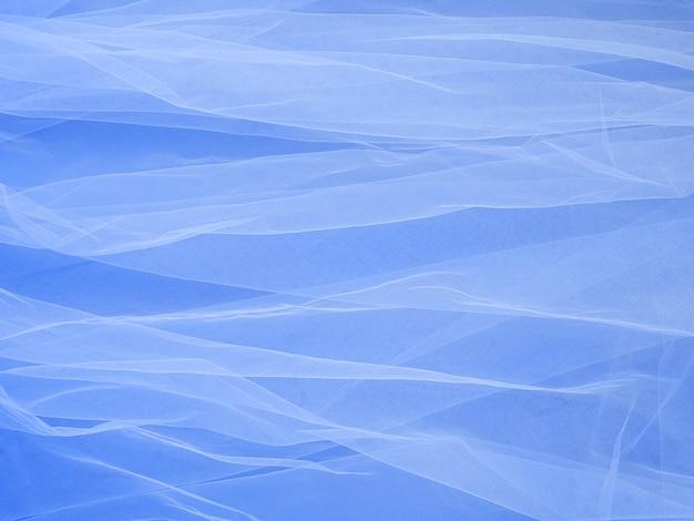 Tissu en maille légère en dentelle sur papier bleu, la texture du tissu est joliment drapée en arrière-plan. toile de fond en voile de mousseline de soie abstraite. concept de mariée. couleur bleu classique de l'année 2020