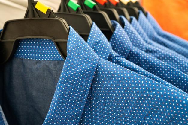 Tissu masculin, rangée de chemises homme bleu sur un cintre dans le placard