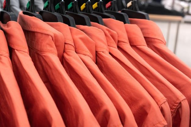 Tissu masculin, rangée de chemises homme rouge sur un cintre dans le placard