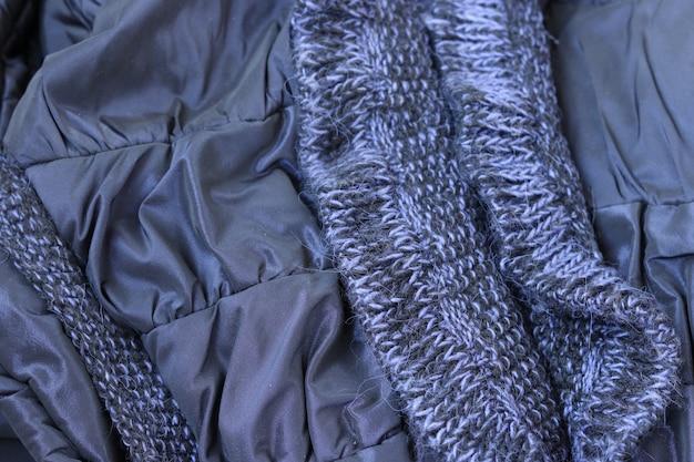 Tissu métallique bleu froissé avec fond d'éléments tricotés