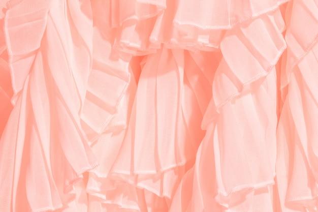 Tissu en mousseline de couleur corail se repliant avec des volants et des volants.