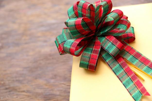 Tissu avec un noeud rouge et vert sur la boîte cadeau d'angle, couleur jaune