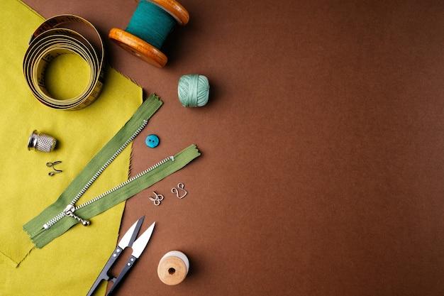 Tissu et outils de couture pour travaux d'aiguille sur fond marron, plat plat, vue de dessus, copiez l'espace.