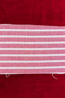 Tissu rayé rose et blanc sur fond de tissu bordeaux
