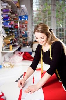 Tissu de robe de coupe de couturière sur la ligne de croquis avec la machine à coudre. boutique de propriétaire d'entreprise et concept d'entrepreneur.