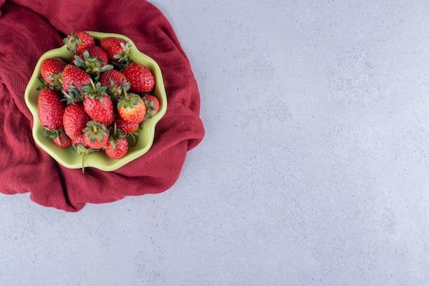 Tissu rouge sous un bol de fraises sur fond de marbre. photo de haute qualité