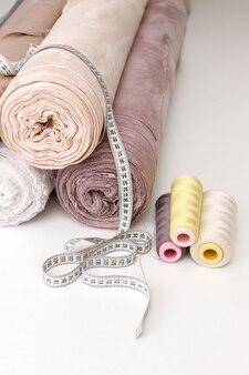 Tissu rulelon avec un centimètre et un fil sur une table blanche