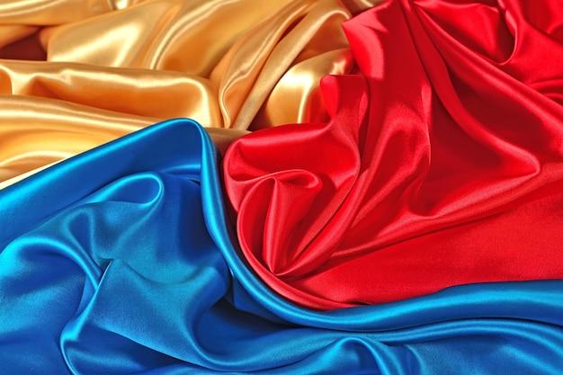 Tissu satiné naturel doré, bleu et rouge comme texture de fond