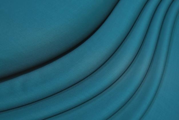 Tissu en soie douce ou texture de tissu satiné. motif de tissu froissé.
