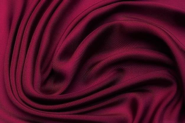Tissu de soie sergé cerise dans une disposition artistique. texture, arrière-plan, motif.