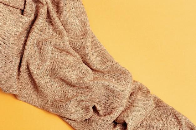 Tissu tricoté beige sur papier jaune. nuances d'automne de tons pastels.