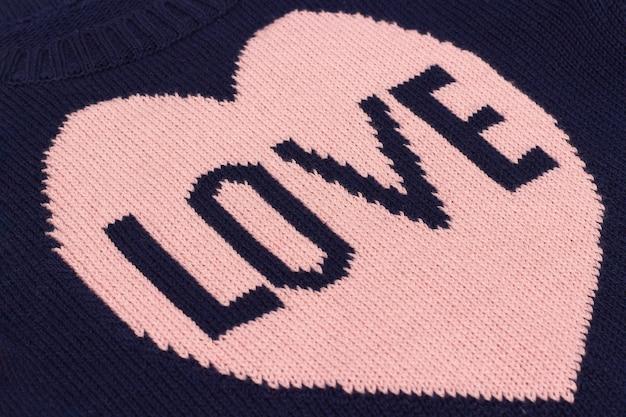 Tissu tricoté bleu fait à la main avec un coeur rose et un mot love lié sur des aiguilles à tricoter