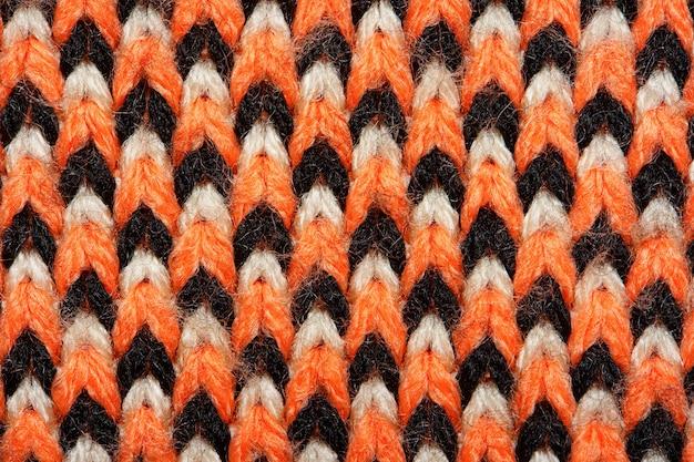 Tissu tricoté synthétique avec des éléments de motif de fils rouges, noirs et blancs se bouchent. contexte